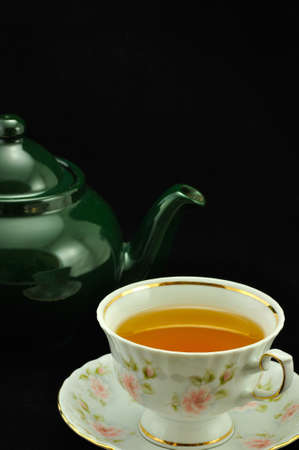 porcelain tea cup full of tea and green teapot on a black background photo
