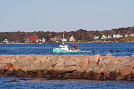 lobster boat: Lobster boat returning to port.  Autumn in South Portland Harbor, Maine.