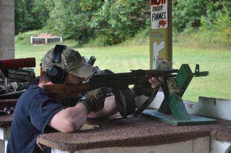 Man Shooting an AK47 AK 47 Assault Gun Rifle at a Shooting Range Stock Photo