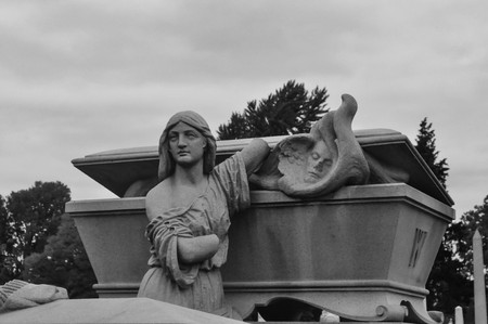 Statue of a mother next to her son's casket in a cemetery