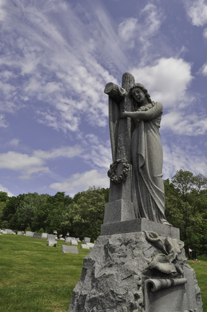 Statue of a Person Holding a Cross in a Cemetery Stock Photo