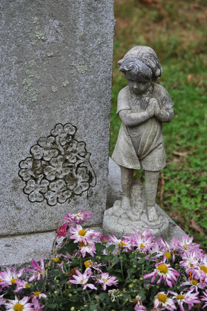 Statue of a Young Girl Looking Down Upon a Grave