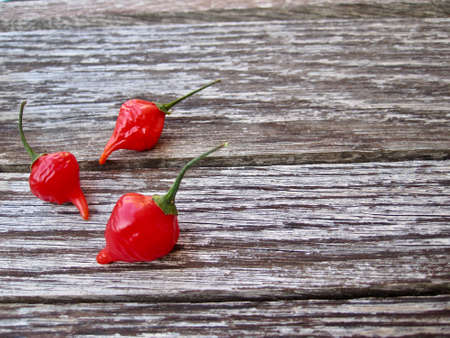 Three chili pepper over an antique table