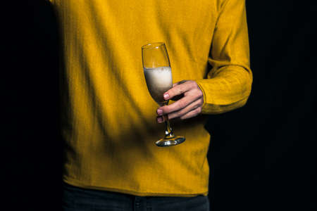 Young man in yellow sweater pour champagne in a glass