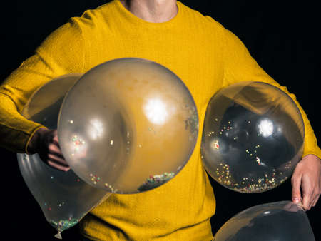 Young man in yellow sweater hold balloons