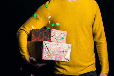 Young man in yellow sweater hold presents