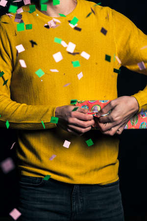 Young man i yellow sweater open present for party