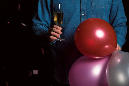 Young man in denim shirt hold champagne and balloons Stock fotó