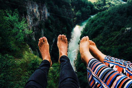 Young couple sitting on the bridge with legs over cliff