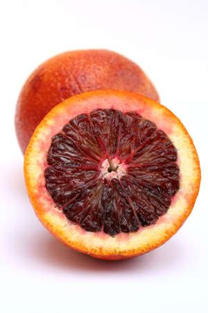 Isolated Image of one blood orange leaning against one whole blood orange