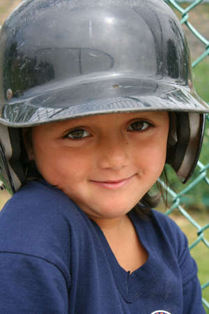 Cute little girl with batting helmet on ready for her turn at bat at her tee-ball game Stock Photo