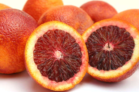to cut: Isolated image of two halves of a blood orange resting against several whole blood oranges