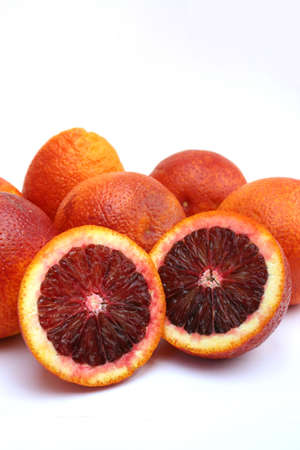 Isolated image of two halves of a blood orange resting against several whole blood oranges