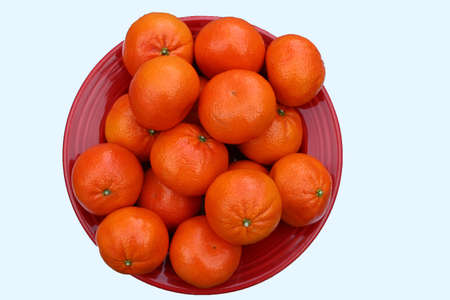 Red bowl filled with orange Clementines Stock Photo