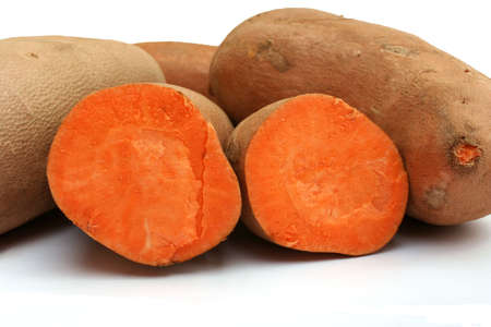 Two halves of a cut sweet potato in front of whole sweet potatoes
