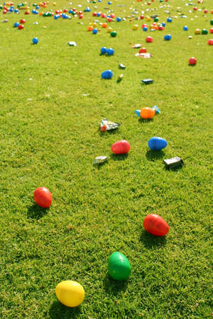 Many Easter Eggs and small candies laid out on grass ready for Children to come and hunt them. Stock Photo