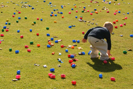 Little Boy bending down to collect an egg in an Easter egg hunt. Stock Photo