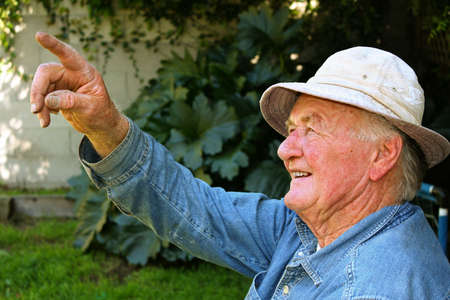Older man pointing to something in his backyard Stock Photo