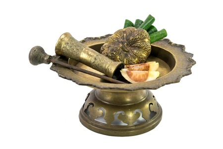 a brass bowl containing betel leaves and areca nuts photo