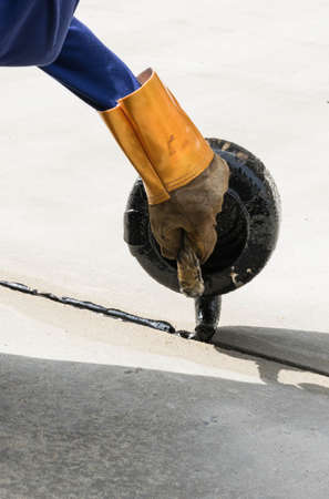 The man worker is pouring asphalt for road repair