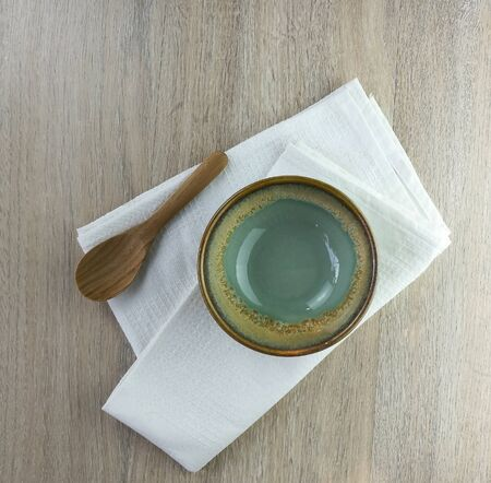 green dishe and wood spoon on a wooden table
