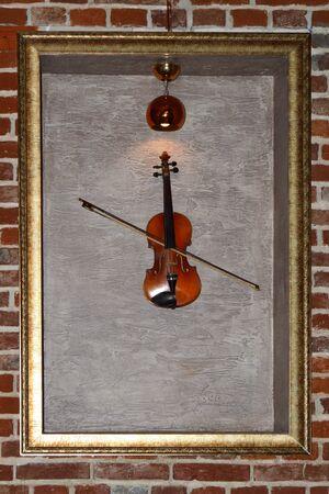 Art display of framed musical instrument on a brick wall Reklamní fotografie