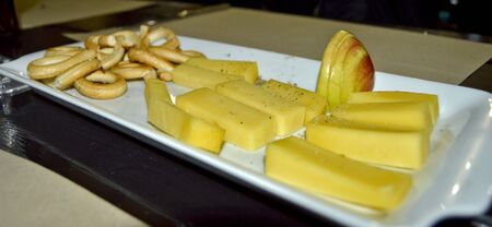 Stock photo of cheese and fruit platter, with thick cheese pieces, apple slices and small pretzels