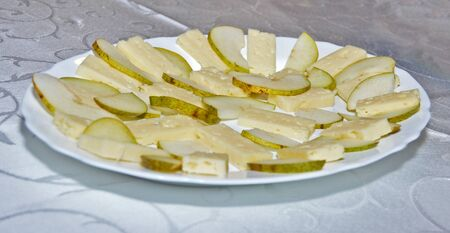 Stock photo of white plate with thin cheese slices paired to sliced pear Stok Fotoğraf