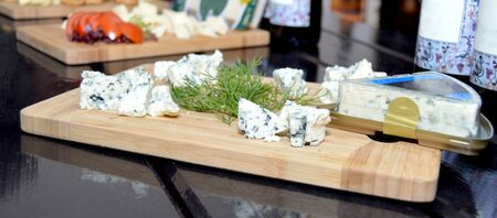 Stock photo of fresh made platter with danish blu cheese pieces and green dill on wooden board