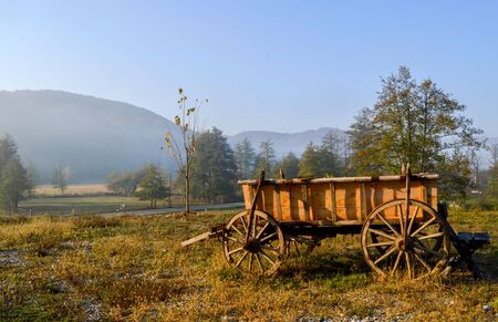 Rural landscape, somewhere in the mountains with warm sunrise light over a field with grass and trees, an old wooden cart with vintage wheels, rustic scenery