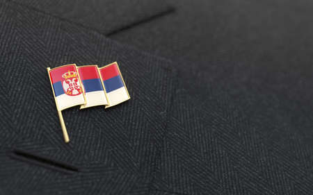 Serbia flag lapel pin on the collar of a business suit jacket shows patriotism photo