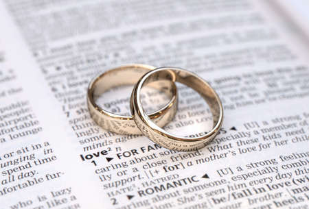 Wedding rings on a dictionary page showing love definition,  close up photo