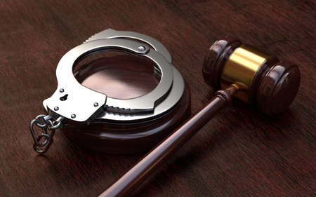 Gavel and handcuffs on wooden, brown table background
