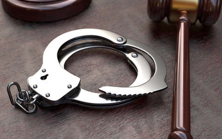 restraints: Gavel and handcuffs on wooden, brown table background