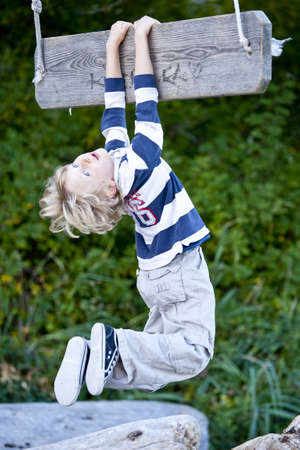A young boy hanging from a swing . Imagens