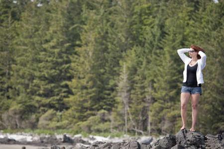 젊은 여자가 바위에 그녀의 위치에서 수평선을 향해 밖으로 보이는