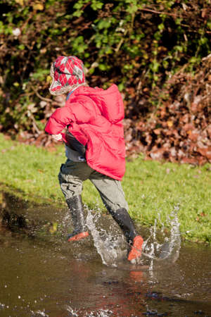 A young boy running through a puddle photo