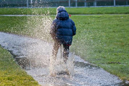 어린 소년은 스쿠터에 웅덩이를 타고 스톡 사진