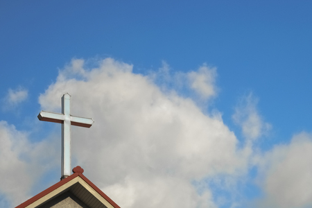 Cross on top of church, with sky and clouds behind