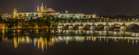 Pretty night time illuminations of Prague Castle, Charles Bridge and St Vitus Cathedral reflected in the Vltava river