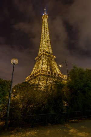 Paris - August 31: Illuminated Eiffel Tower at night with some clouds on August 31, 2013 in Paris, France