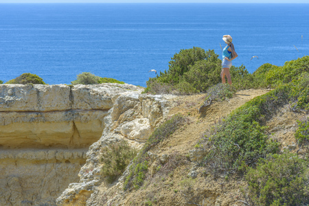 Female tourist looking at the Atlantic Ocean in Algarve, Portugal. 版權商用圖片