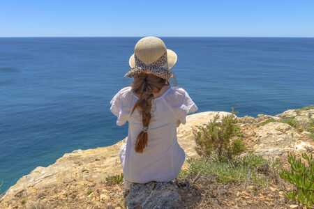 Tourist enjoying the ocean view from a cliff in Algarve, Portugal Imagens