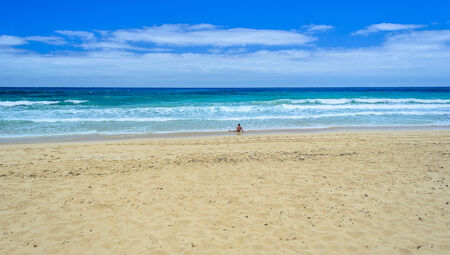 Tourist relaxing at Corralejo beach in Fuerteventura, Canary Islands.