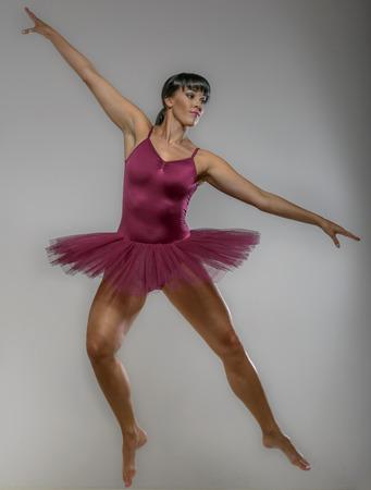 Ballet Dancer jumping high against a white background.