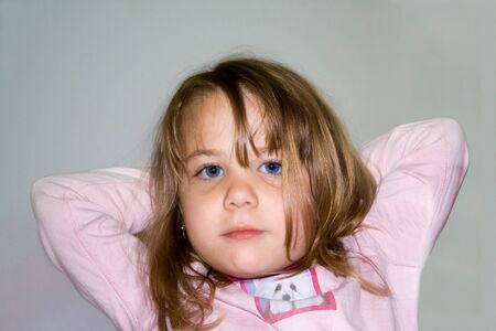 Young girl with arms folded behind head and blue eyes.