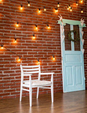 wooden color: white chair against a background of a brick wall with a garland Stock Photo