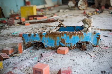Abandoned kindergarten in Chernobyl Exclusion Zone. Lost toys, A broken doll. Atmosphere of fear and loneliness. Ukraine, ghost town Pripyat.