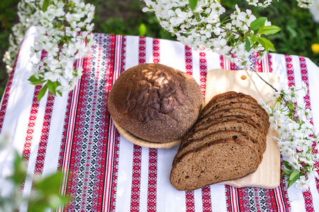Rye bread on a wooden board against a background of with blooming cherry branches. fresh bread on a background of flowering trees 版權商用圖片 - 122573491
