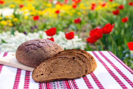 Rye bread on a wooden board against the background of spring flowers. fresh bread on a background of blooming tulips Stock Photo